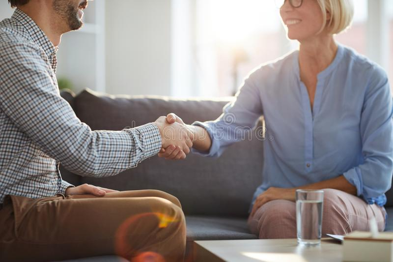 Saying thanks. Successful counselor shaking hand of mature female patient while both sitting on couch after consultation stock photo