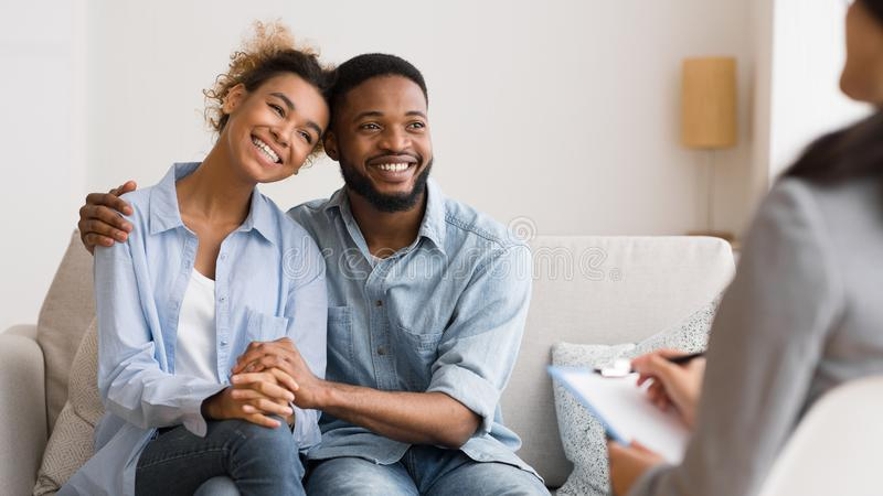 Positive African American Couple Hugging After Reconciling At Psychologist`s Office. Successful Couples Therapy. Afro Spouses In Love Hugging After Making Up royalty free stock photo