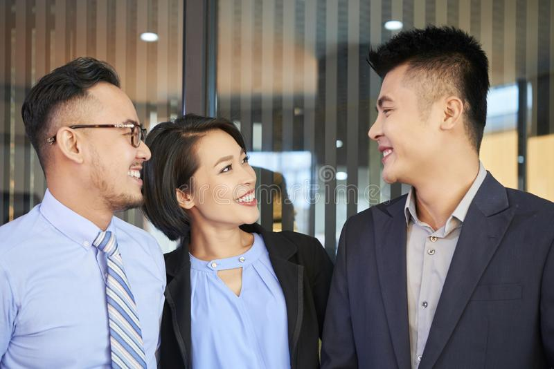 Successful coworker. Smiling Asian business people looking at their successful colleague with admiration royalty free stock image