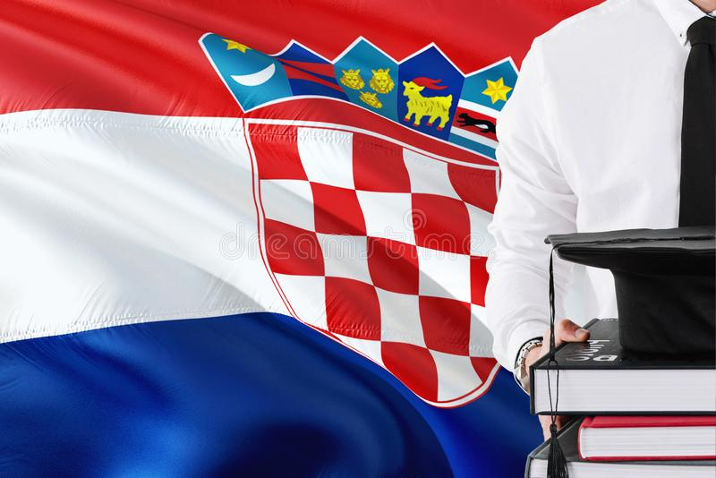 Successful Croatian student education concept. Holding books and graduation cap over Croatia flag background.  royalty free stock photography