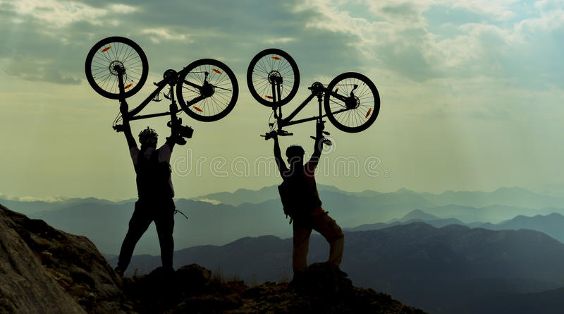 Successful cyclists at the peak of the mountain royalty free stock photo