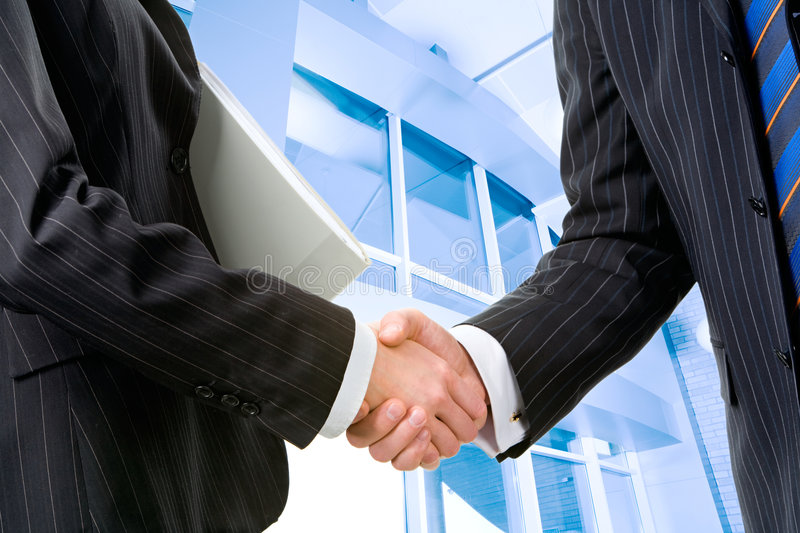 Successful deal. Two partners shaking hands at meeting in front of building stock images