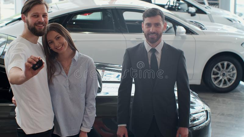 Successful deal between car salesman and young couple in car dealership. royalty free stock photo
