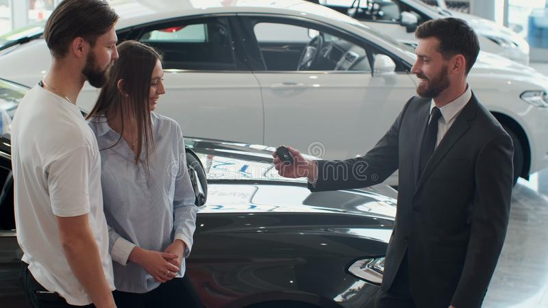 Successful deal between car salesman and young couple in car dealership. royalty free stock images