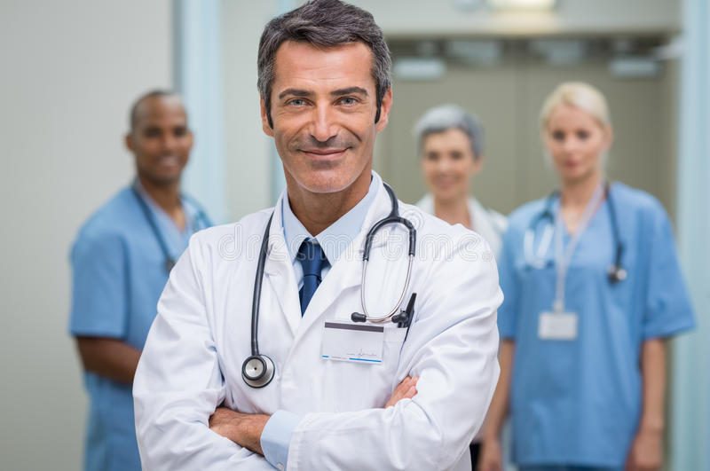Successful doctor and his staff. Portrait of happy mature doctor standing in corridor with team at hospital. Smiling doctor with crossed arms looking at camera royalty free stock photos