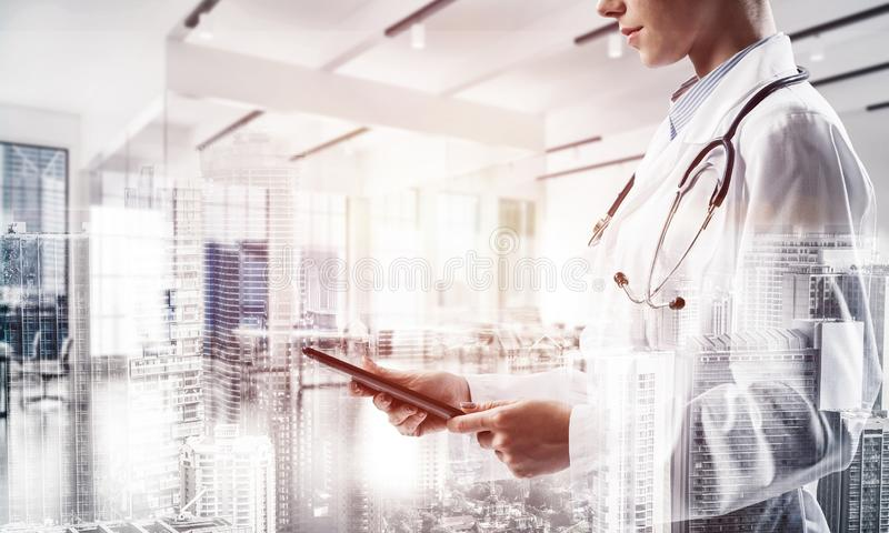 Successful doctor and modern technologies. Double exposure of confident female doctor in white coat standing at hospital building with laptop in hands and vector illustration