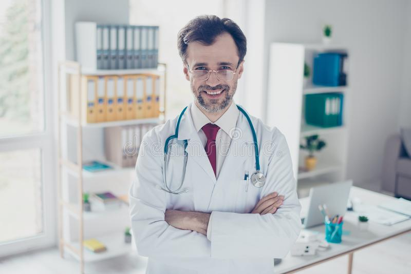 Successful doctor in white uniform is standing at his workplace stock image