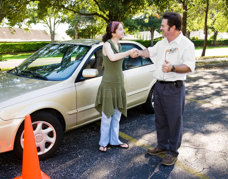 Successful Driving Test. Driving instructor congratulates teen student on passing the drivers test royalty free stock image