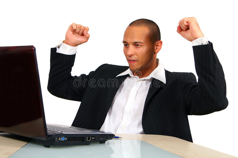 Successful E-Business. A young satisfied businessman sitting in front of his laptop his hands in the air at the table celebrating his success. Isolated over stock image