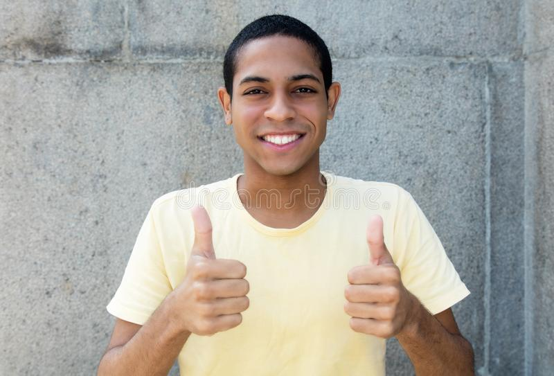 Successful egyptian young adult man showing both thumbs up royalty free stock photo