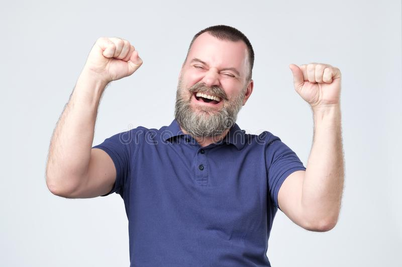 Successful emotional mature man screaming Yes and raising clenched fists in the air royalty free stock images