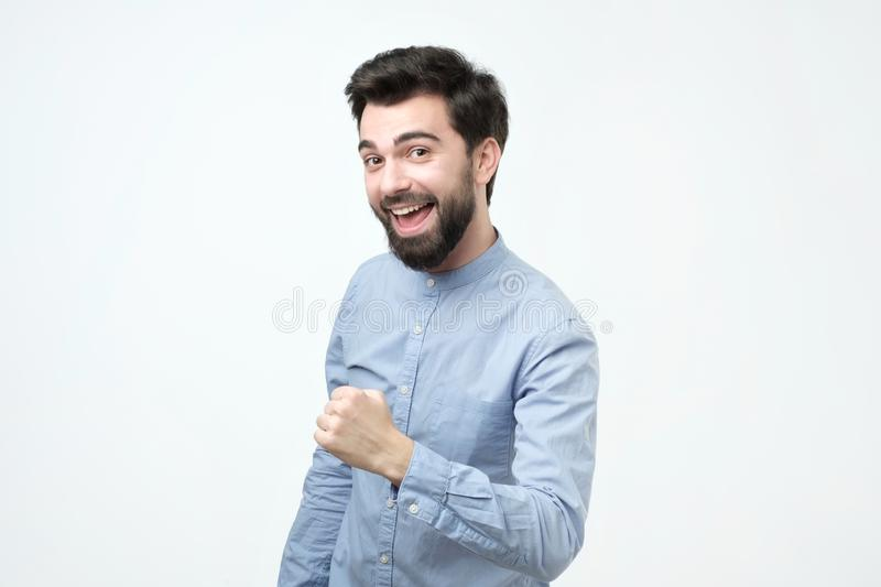 Successful emotional young hispanic man with dark hair screaming Yes and raising clenched fist royalty free stock photos