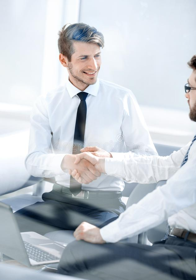 Successful employees shaking hands sitting at the Desk stock photography