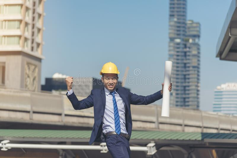 Successful engineer finishing project complete. holding fist and construction blue print in the air sign of victory. Success stock images