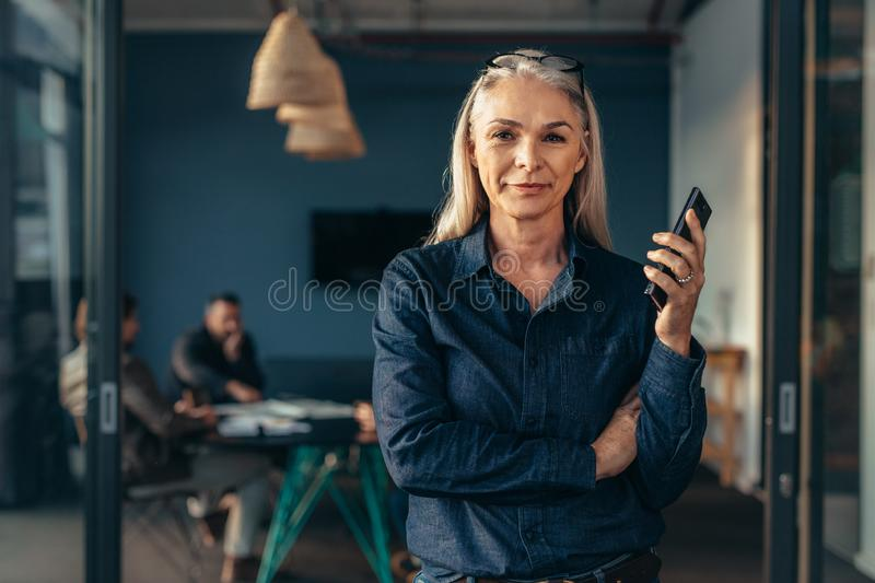Successful entrepreneur in office with team at back stock photos