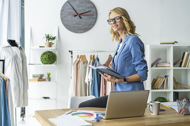 Successful fashion designer. attractive young woman standing in workshop royalty free stock images