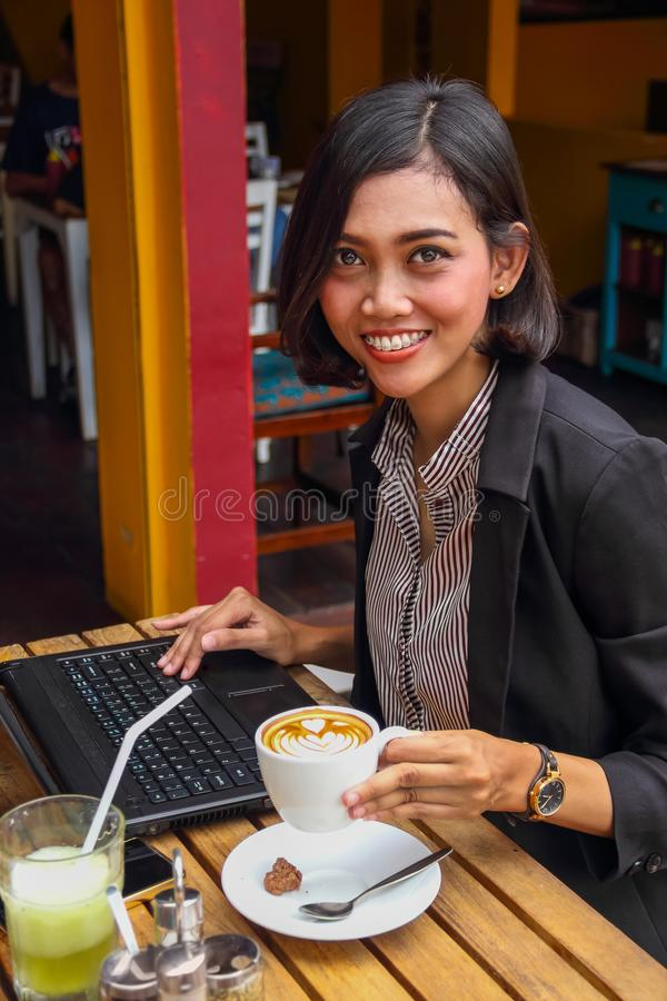 Successful female entrepreneur works outside, holding a cup of coffee stock photography