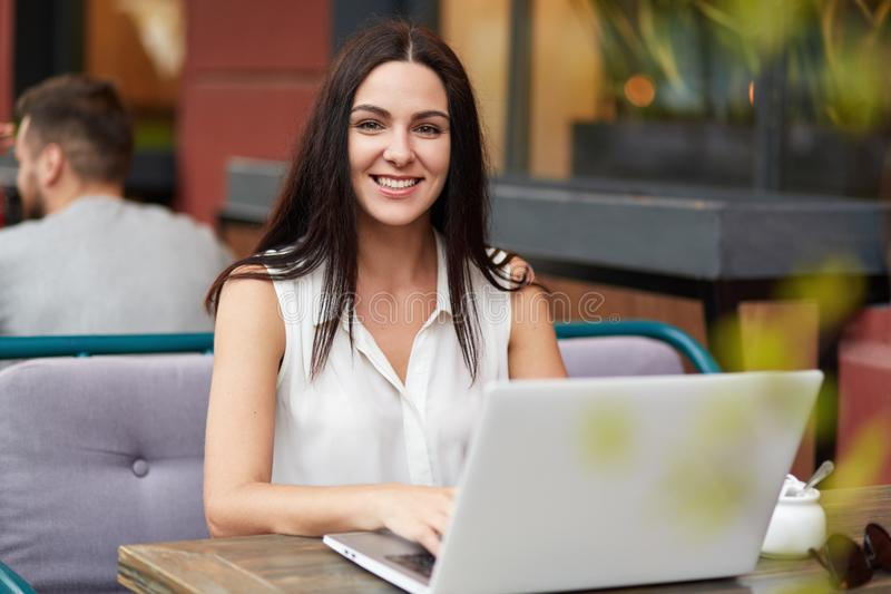 Successful female freelancer works remotely on laptop computer, sits in outdoor cafe, has pleasant smile, enjoys remote work, look stock photos