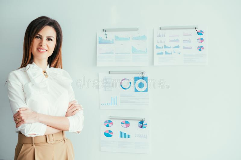 Successful female leader confident project manager. Successful female leader. Confident project manager. Young brunette woman standing at whiteboard with graphs stock images