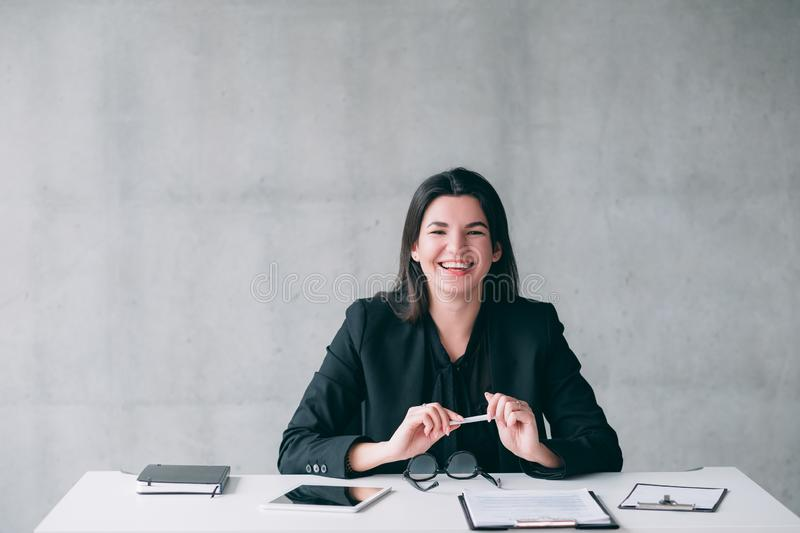 Successful female leader happy business woman. Successful female leader. Happy business woman sitting at office desk, smiling. Cheerful facial expression stock photo