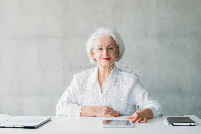 Successful female leader woman modern technology. Successful female leader. Modern technology in educational process. Portrait of senior woman sitting at desk royalty free stock photography