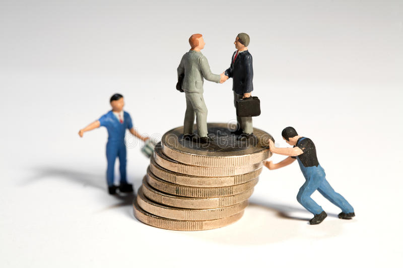 Successful Financial Agreement. Miniature toy figures of businessmen shaking hands standing on top of of a large pile of Euro coins being moved by workmen royalty free stock photo