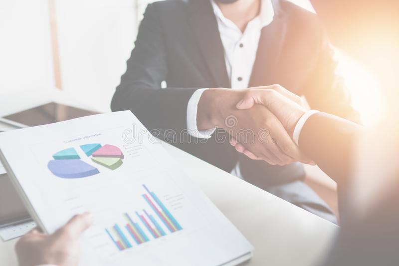 Successful financial business, businessman holding graph reports and shake hands with lead generator manager, teamwork of royalty free stock images