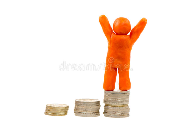 Successful Financial Winner. Successful winner on the top - self-made human plasticine figure standing on top of a stack of coins royalty free stock photo