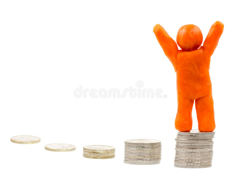 Successful Financial Winner. Successful winner on the top - self-made human plasticine figure standing on top of a stack of coins royalty free stock image