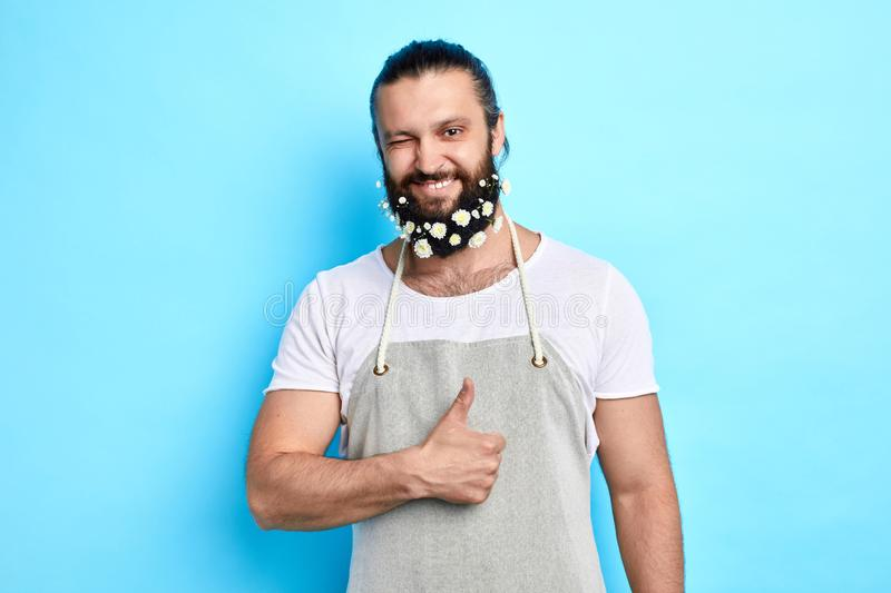 Successful gardener with fubby creative beard giving a wink at the camera. Close up portrait. isolated blue background. studio shot stock photo