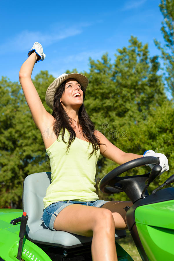 Successful gardener riding garden tractor. Successful and happy female gardener riding garden tractor and raising arm. Woman riding lawn mower. Girl working on royalty free stock photo