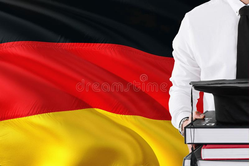 Successful German student education concept. Holding books and graduation cap over Germany flag background stock images