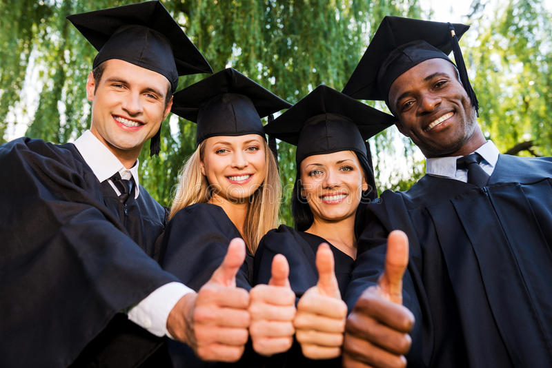 Successful graduates. Low angle view of four college graduates in graduation gowns standing close to each other and showing their thumbs up royalty free stock images
