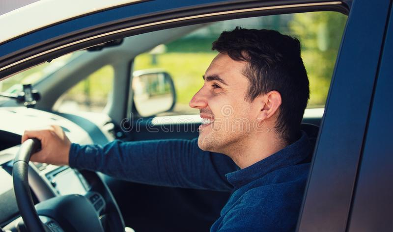 Successful guy confident smiling, enjoying the ride, traveling road trip concept. Happy young man driving his new car keeps hand on the steering wheel looking royalty free stock photography