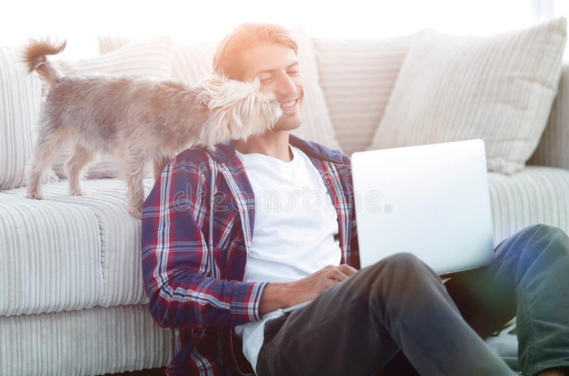 Successful guy and his favorite pet in a cozy living room. royalty free stock photography