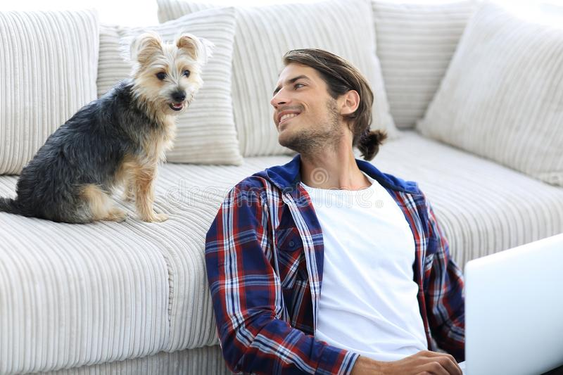 Successful guy and his favorite pet in a cozy living room. royalty free stock image
