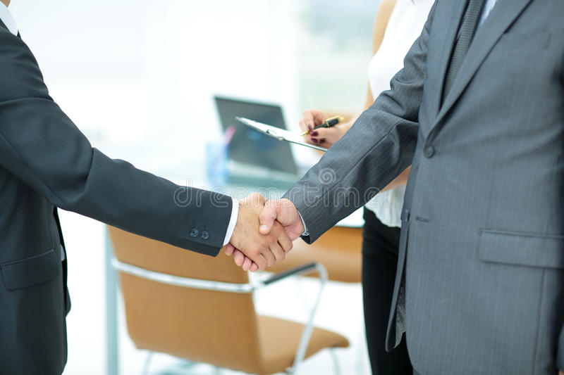 Successful handshake of business men in a working environment stock images