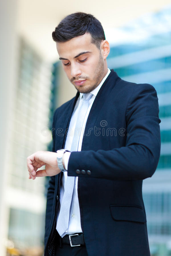 Successful handsome businessman looking at his watch stock photography