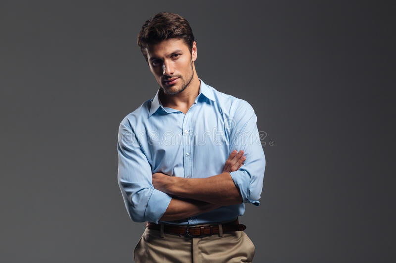 Successful handsome man with arms folded standing. Isolated on a gray background and looking at camera royalty free stock images