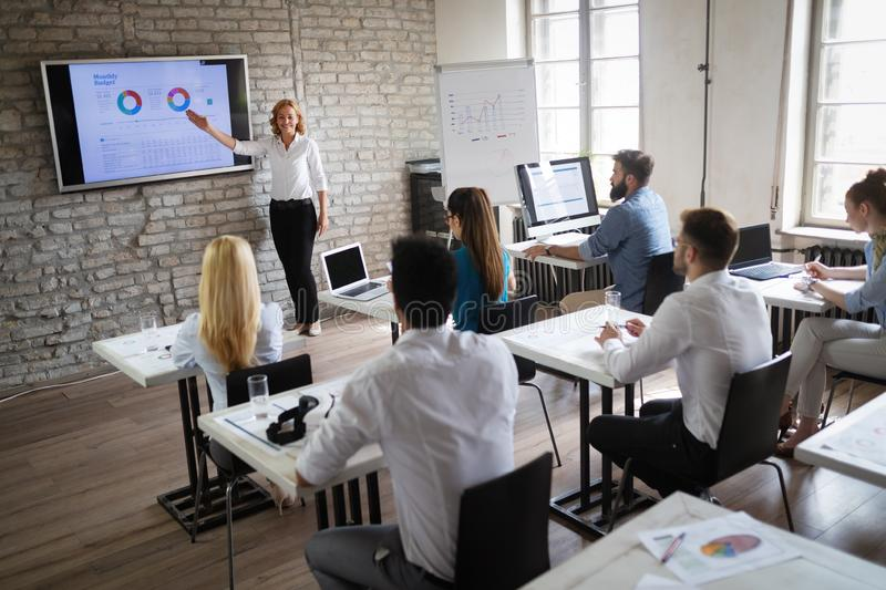 Successful happy group of people learning software engineering and business during presentation royalty free stock images