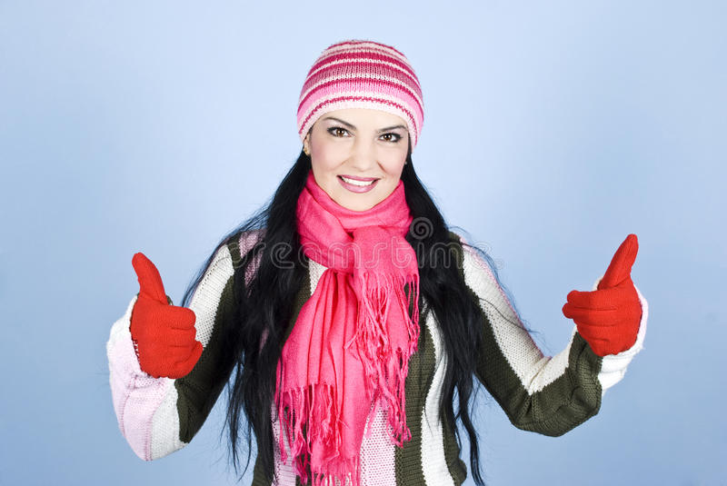 Successful happy winter woman. Giving thumbs up with gloves in hands and smiling for you in front of blue background,check also my photos in this collection royalty free stock images