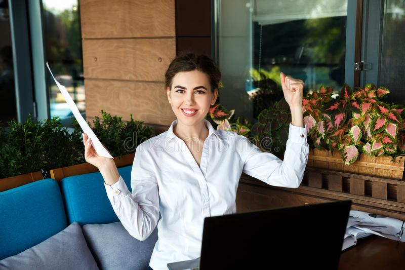 Successful happy young woman working on laptop in cafe outdoor royalty free stock images