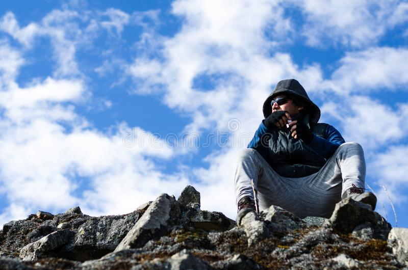 Successful hiker man enjoys the view on top of the mountain royalty free stock images