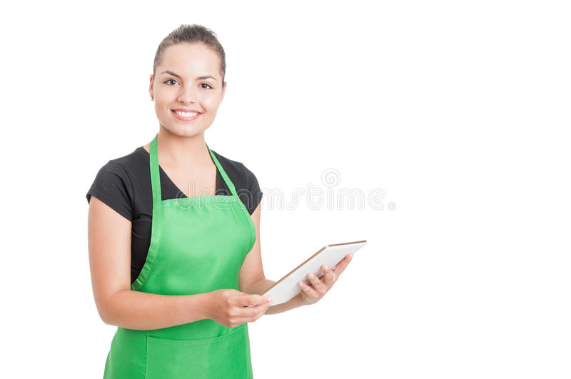 Successful hypermarket employee holding modern tablet. Successful hypermarket employee with green apron holding modern tablet isolated on white background with royalty free stock image