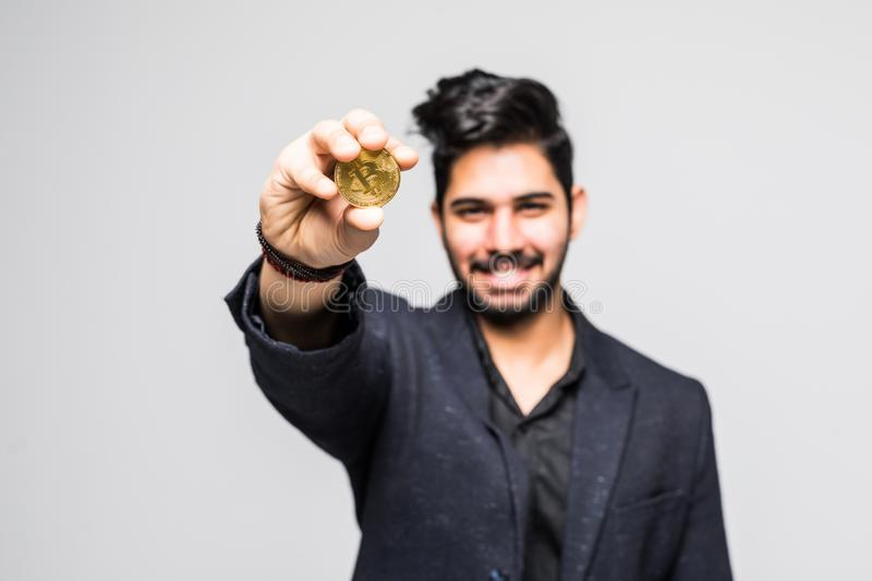 Successful indian man in suit pointing f golden bitcoin isolated over white background royalty free stock photos