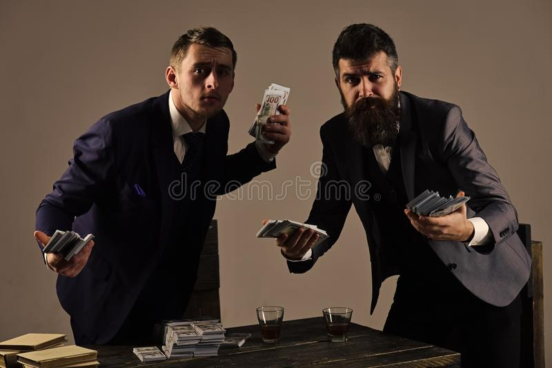 Successful investment. Clandestine transaction with cash. Company engaged in illegal business. Men at table with piles royalty free stock photography