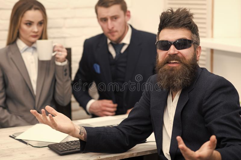 Successful job interview concept. Man with beard in sunglasses smiling, bosses, coworkers, colleagues on background. Man royalty free stock image