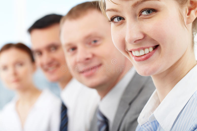Successful leader. Portrait of friendly leader looking at camera with three employees behind stock photo