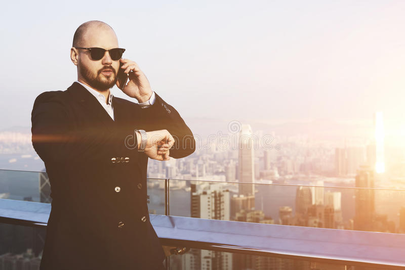 Successful male CEO having cell telephone conversation. Young rich man in sunglasses is checking time on watches and talking on mobile phone,while is standing on stock photos