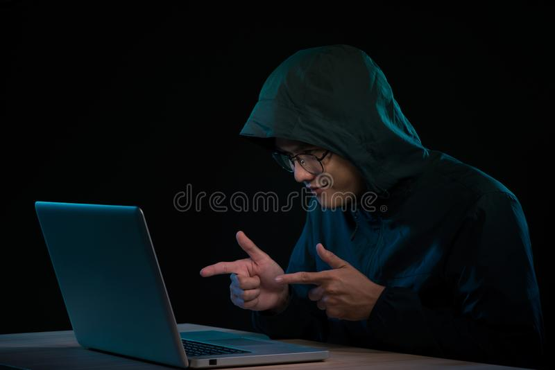 Successful male hacker poses in front of laptop computer, clenches fists, dressed in black clothes, rejoices finishing bad data. Virus royalty free stock photo